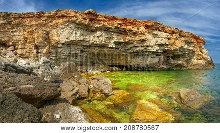 Rocky precipitous seashore beautiful lagoon with saturated water