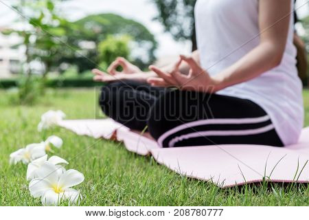 Young attractive asian girl practice yoga and relax in the park healthy concept.