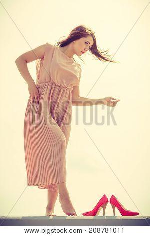 Hobby idyllic aspects of femininity concept. Woman walking on jetty without shoes wearing beautiful long light pink dress.