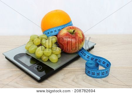 Fruits are apple orange grapes and meter on electronic scales. Diet.