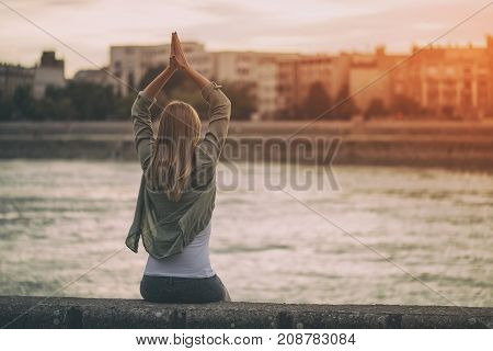 Young woman enjoys meditating at the riverbank.