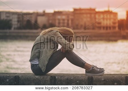 Image of sad woman sitting at the riverbank.