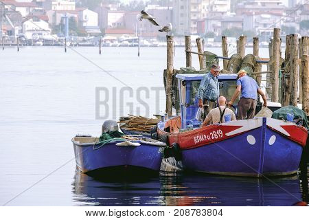 Chioggia Italy - 04 October 2017: Older fishermen return to the port on their boat after a day of work at sea