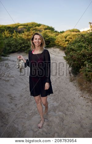 Attractive slender blond woman carrying her shoes as she walks along a sandy beach path smiling happily to the side on summer vacation