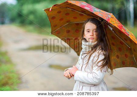 little girl is walking under an umbrella in a park autumn weather