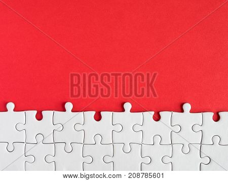 Group of white jigsaw puzzle on red background in top view (Business Concept)