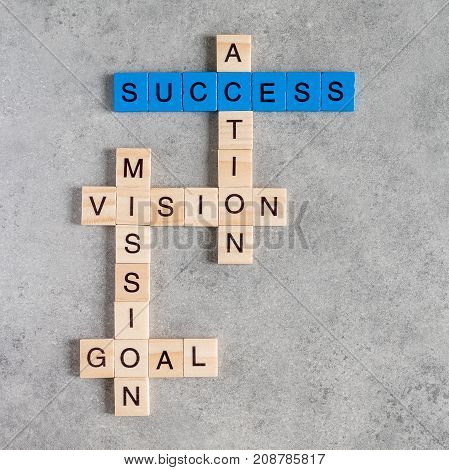 Wooden cubes crossword of Success Vision Mission Goal Action on wood background
