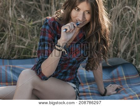 Beautiful brunette girl in the field, shirt shorts. Concept of new ideas, Happy in the fresh summer in nature. In his hand a notebook, long hair. To study notes in the diary.