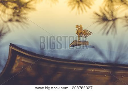 Gold Chinese phoenix bird on roof that covered white snow of Golden Pavilion at Kinkakuji Temple with sunlight and blue sky background in winter season, Kyoto, Japan.