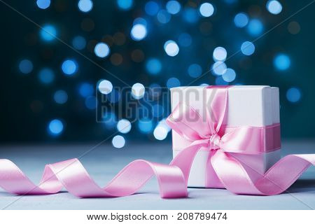 Small gift box or present with pink bow ribbon against magic bokeh background. Greeting card for Christmas New Year or wedding.