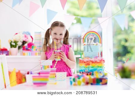 Kids birthday party with colorful pastel decoration and unicorn rainbow cake. Little girl with sweets candy and fruit. Balloons and banner at festive decorated table for child or baby birthday party.