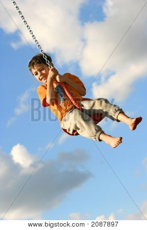 Young Boy On Chain Swing Enjoying The Park