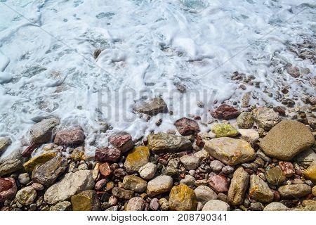 Sea waves sea foam break up on the coastal stones.