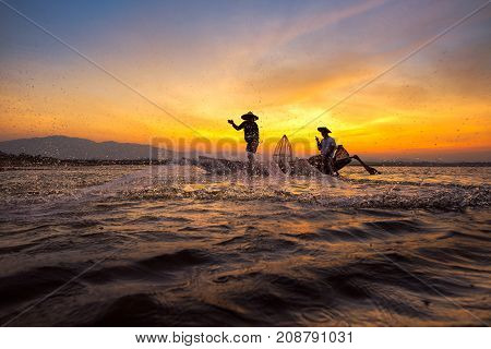 Silhouette asian fisherman on wooden boat casting a net for catching freshwater fish in nature river in the early morning before sunrise.