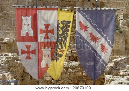 Three old Crusaders flags and coat of arms in the castle of Acre on the Mediterranean coast of Israel