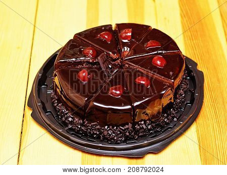 Delicious chocolate cake sliced in portions with fresh cherries.