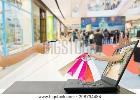 hands holding bags shopping buy online and laptops and credit cards