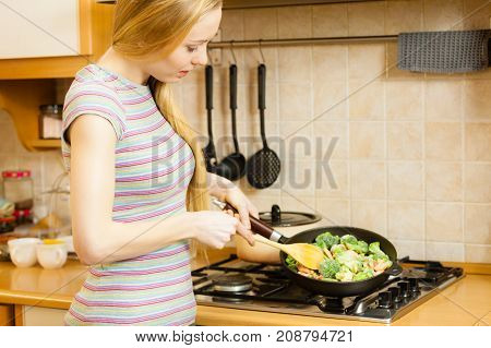 Woman Cooking Stir Fry Frozen Vegetable On Pan