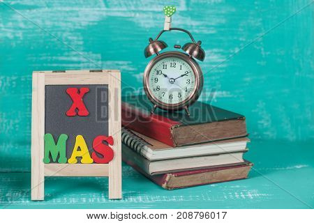 X Mas Text On Blackboard With Old Book And Clock