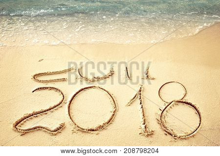 New Year 2018 replace 2017 on sea beach summer, New Year 2017 is coming concept. Closeup
