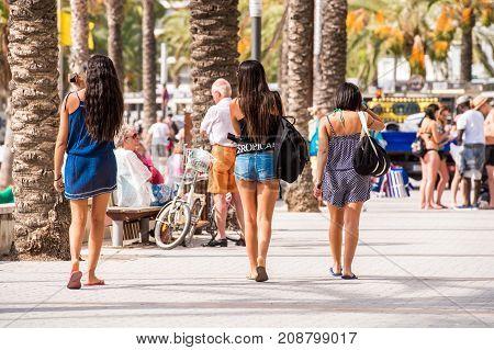 People Walk Along The Embankment, Salou, Tarragona, Spain. Copy Space For Text.