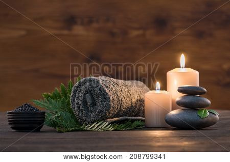 poster of Towel on fern with candles and black hot stone on wooden background. Hot stone massage setting lit by candles. Massage therapy for one person with candle light. Beauty spa treatment and relax concept.
