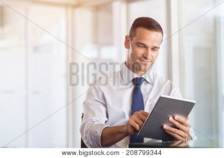 Smiling businessman using digital tablet at work. Portrait of a happy formal man working on computer in a modern office. Satisfied business man sitting at desk and checking the email.