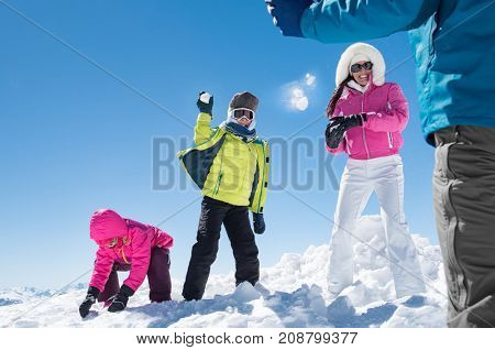 Family having snowball fight in mountain during winter holiday. Family throwing snowballs on each other. Mother and children throwing snowball to father. Smiling family having fun together in winter.