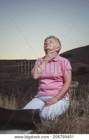 senior woman make a breath exercises at evening in mountains