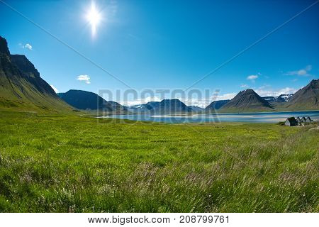 Travel to Iceland. beautiful sunrise over the ocean and fjord in Iceland. Icelandic landscape with mountains, blue sky and green grass on the foreground. View of Flateyri, a village in the north-west of Iceland, on the Westfirdir peninsula