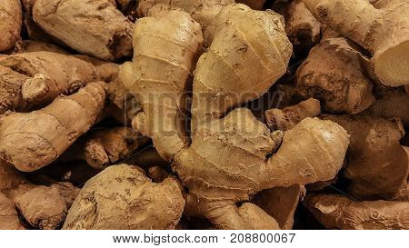 Fresh organic ginger stand out among many large background ginger in the market. Heap of ginger root. Close-up ginger texture.