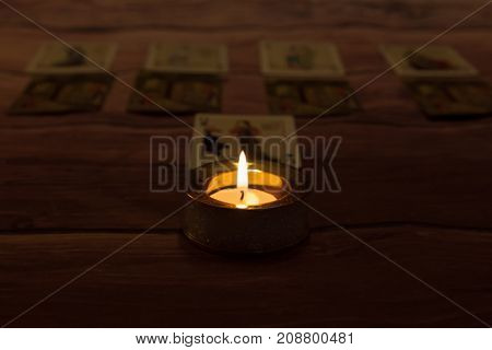 Mystic fired candle with playing cards in darkness on wooden background