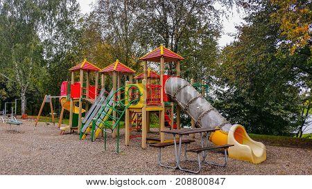 Colorful children playground activities in public. Children run slide swing on modern playground. Urban neighborhood childhood concept.