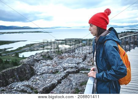 Girl in warm clothing observing surroundings on background of lake and mountains of Iceland.