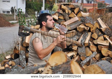 Tired lumberjack get rest and drink water. Lumberjack drink cold water to refresh after hard work