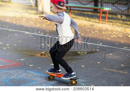 Little Urban Boy With A Penny Skateboard. Young Kid Riding In The Park On A Skateboard. City Style.
