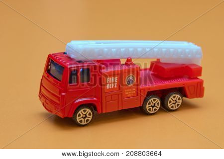 Red toy fire truck Toy fire engine extinguishes flaming house. Careless handling of fire dangerous for life miniature red color fire truck on yellow background toy car selective focus copy space