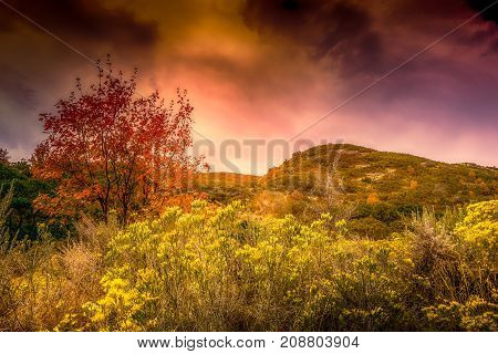 Mountain foothills in Autumn with a dramatic stormy sky
