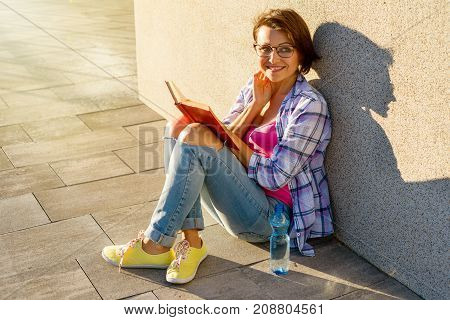 Smiling adult female drinking water and reading a book. Recreation in the city and health