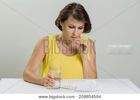 Adult woman looking at instructions holding a package of pills. Age medicine health care and people concept