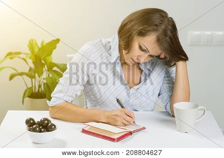 Adult woman with a notebook sitting at a table with a cup of tea