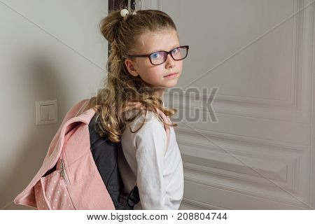 Cute junior schoolgirl with blond hair going to school standing next to door