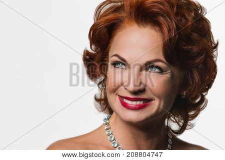 Beautiful Mature redhead woman in the image of Marilyn Monroe.The picture was taken in a studio on a white background.