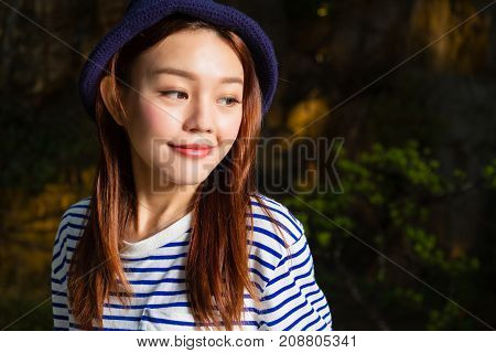 Chinese woman looking away with defocused nature background