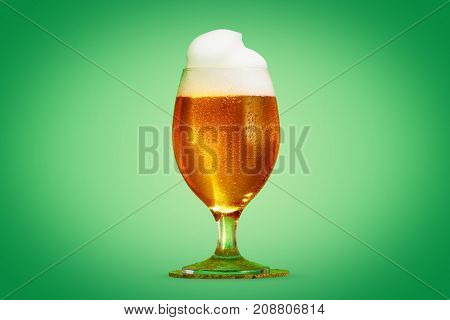 Glass pint of beer close-up with froth over green background