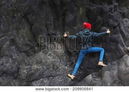 woman rock climber. rock climber climbs on a black rocky wall on the ocean bank in Iceland, Kirkjufjara beach. woman makes hard move without rope.