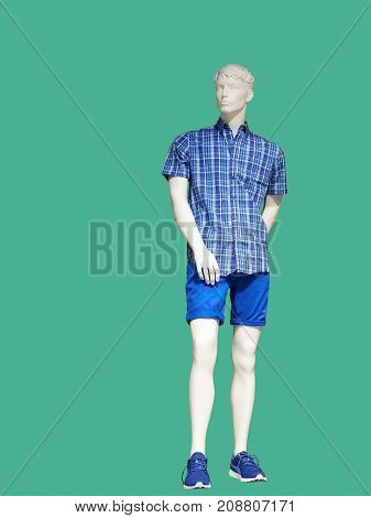Full-length man mannequin dressed in casual clothes over green background. No brand names or copyright objects.
