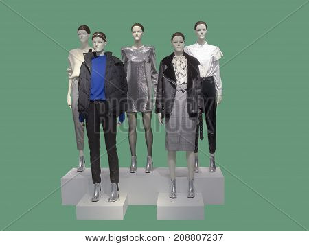 Group of female mannequins wear fashionable clothes isolated on green background. No brand names or copyright objects.