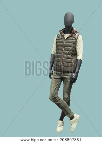 Full-length man mannequin dressed in sleeveless quilted jacket and jeans isolated on green background.