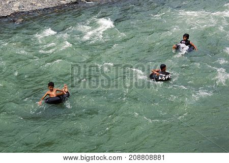 SUMATRA INDONESIA - AUGUST 17 2012:Boys raft on automobile rubber tires on a mountain river